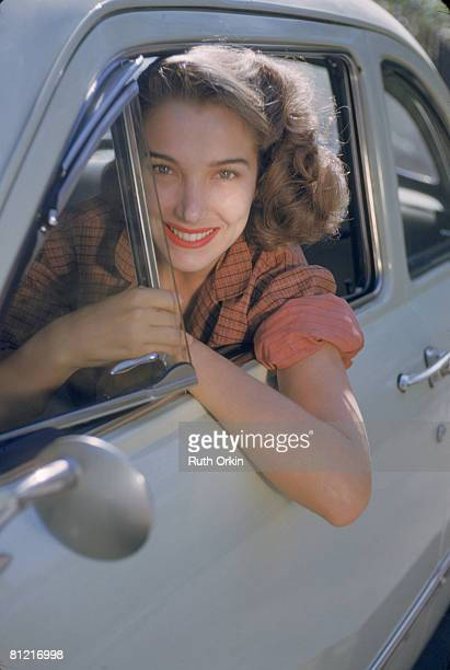 Portrait of American actress Julie Adams as she leans out of the window of a car early 1950s