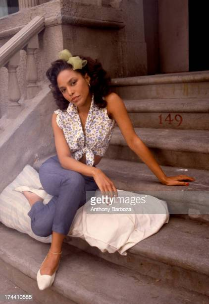 Portrait of American actress Lynn Whitfield as she poses seated on a pillow on a stoop on the set of the television miniseries 'The Women of Brewster...