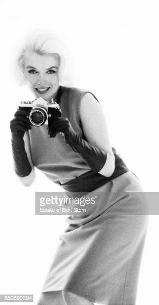 Portrait of American actress Marilyn Monroe as she aims a Nikon camera Beverly Hills California July 1962 The two sessions for this photoshoot took...