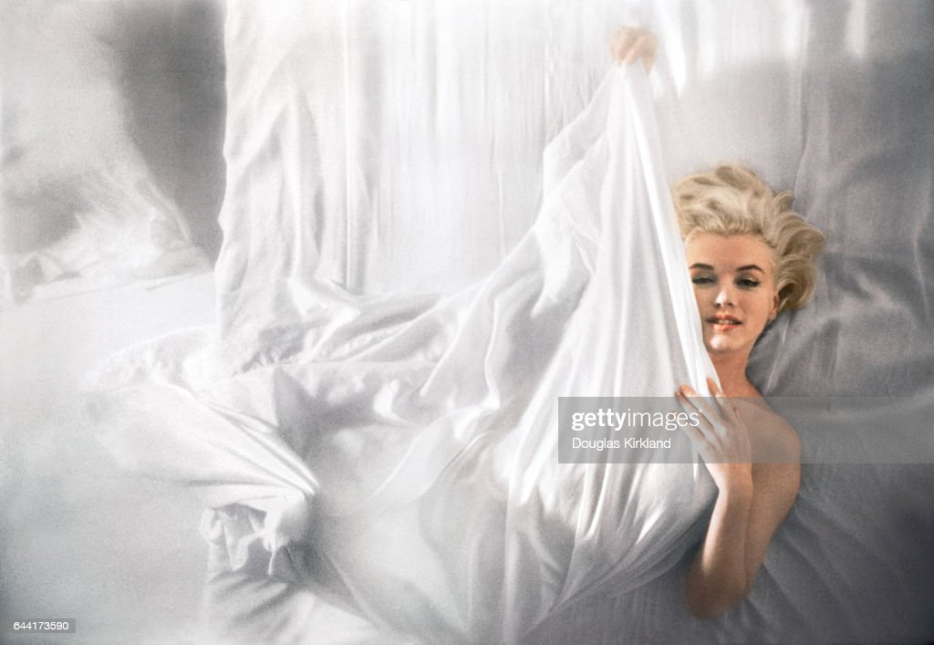 Movie star Marilyn Monroe wraps herself in a white sheet on a bed.