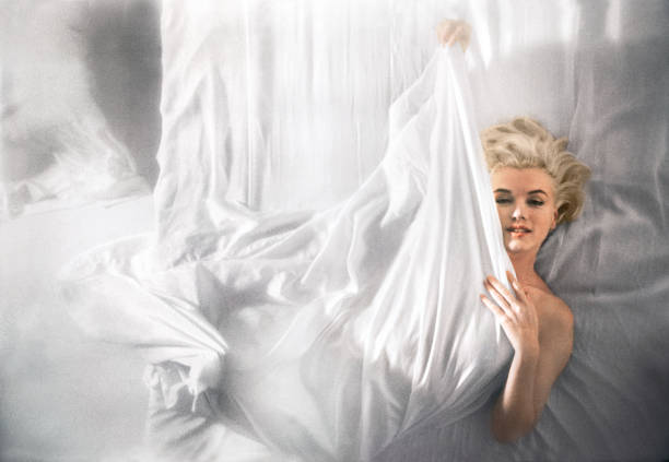 Portrait of American actress Marilyn Monroe as she lies on a bed wrapped in a white sheet Hollywood Los Angeles California November 1961