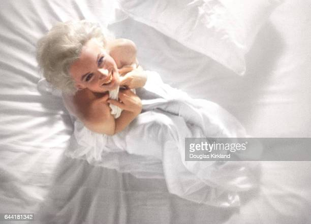 Movie star Marilyn Monroe wraps herself in a white sheet on a bed