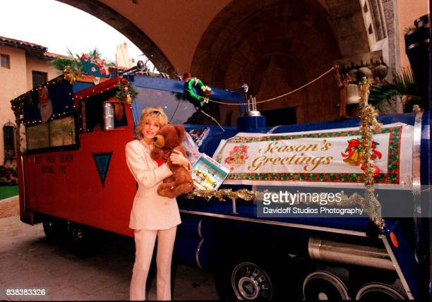Portrait of American actress Marla Maples hugs a teddy bear as she poses beside a vehicle decorated as a Christmas train with a banner that reads...