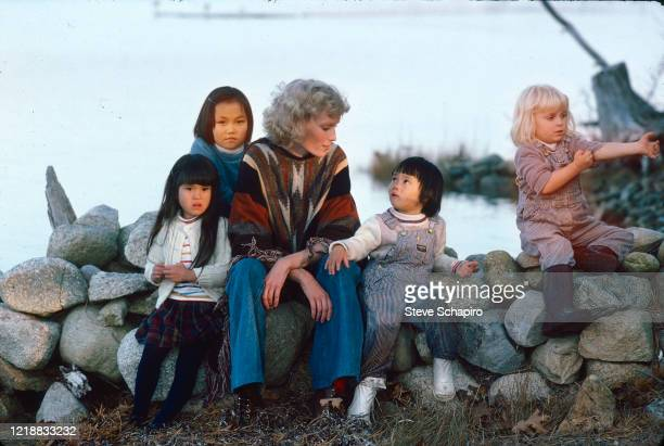 Portrait of American actress Mia Farrow as she poses outdoors, seated on a low wall, with her children, Martha's Vineyard, Massachusetts, 1979....