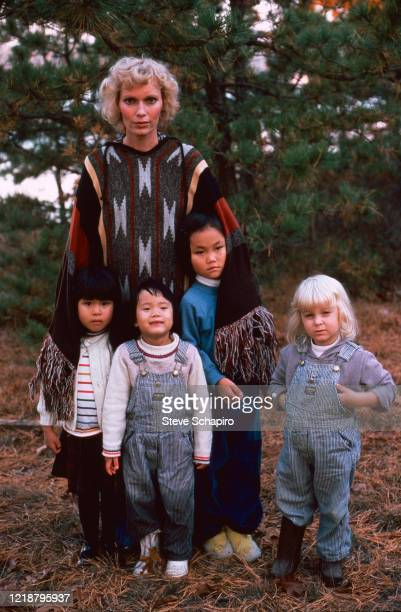 Portrait of American actress Mia Farrow as she poses outdoors with her children, Martha's Vineyard, Massachusetts, 1979. Pictured are, fore from...