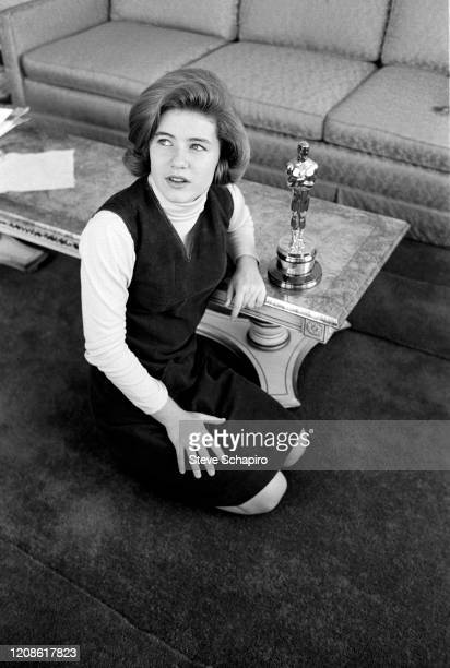 Portrait of American actress Patty Duke as she kneels beside a coffee table with her Academy Award New York New York 1964 She had won the award for...