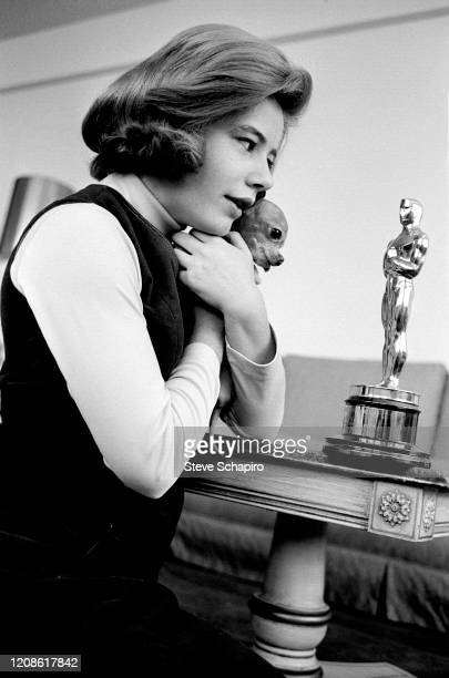 Portrait of American actress Patty Duke her pet dog Bambi in her arms as she kneels beside a coffee table with her Academy Award New York New York...