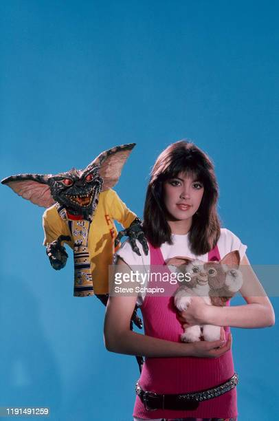 Portrait of American actress Phoebe Cates as she poses with pair of creatures, one a 'gremlin' and the other a 'mogwai' , from the film 'Gremlins' ,...