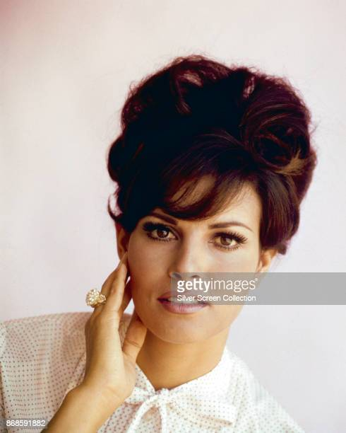 Portrait of American actress Raquel Welch as she poses, one hand on her cheek, against a white background, 1965.