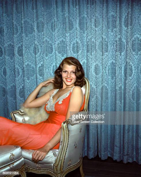 Portrait of American actress Rita Hayworth in an embroidered sheer orange nightgown as she sits in a chair mid 1940s