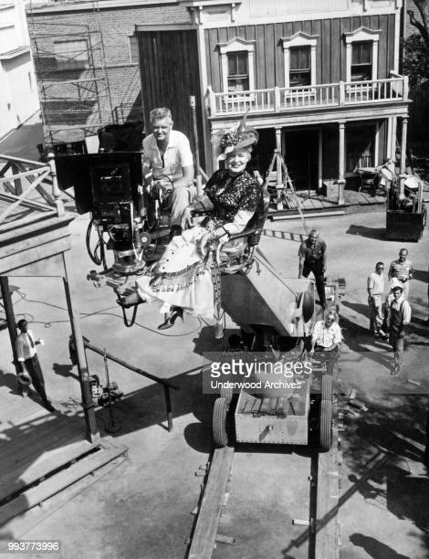 Portrait of American actress Shirley Booth in full costume and cinematographer Charles Lang as they sit on a camera boom above the backlot set of the...