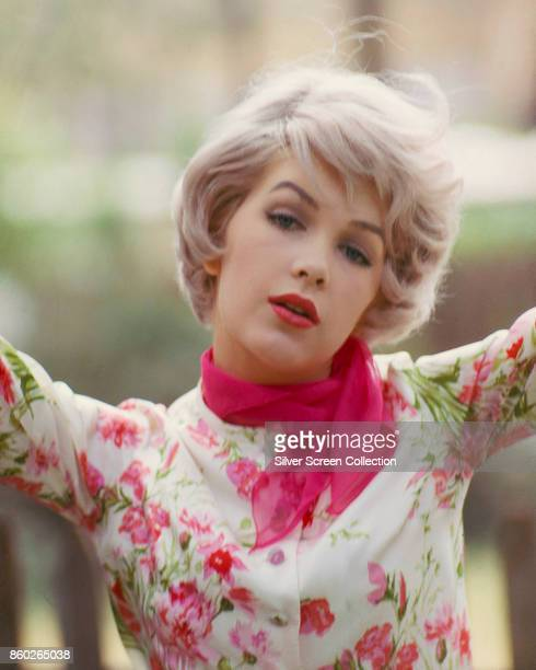 Portrait of American actress Stella Stevens in a flower print top and pink scarf late 1960s