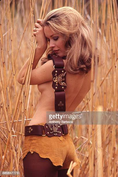 Portrait of American actress Tanya Roberts as she poses topless dressed in buckskinlike shorts and pantyhose with one belt at her waist and another...