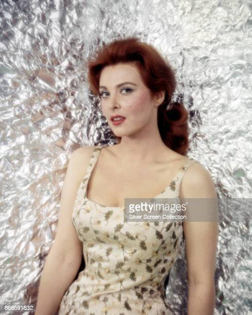 Portrait of American actress Tina Louise in a flowerprint dress as she poses against a silver backdrop early 1960s