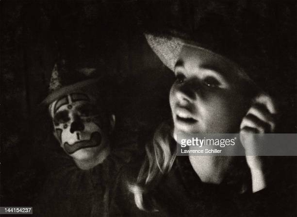 Portrait of American actress Tuesday Weld at Canter's Deli Los Angeles California June 1963 A person in clown makeup is next to her