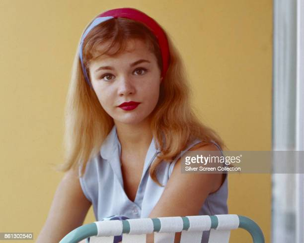 Portrait of American actress Tuesday Weld in a blue sleeveless top and a red blue headband as she sits in a deckchair late 1950s