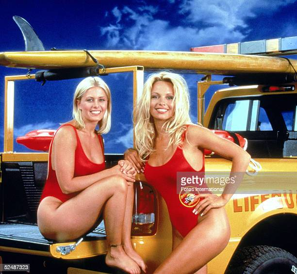 Portrait of American actresses Nicole Eggert and Pamela Anderson stars of the tv series 'Baywatch' wearing lowcut red swimsuits 1992