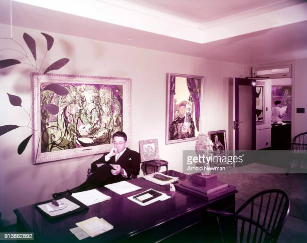 Portrait of American advertising executive and art collector Earle Ludgin as he sits behind a desk in an unspecified gallery surrounded by various...