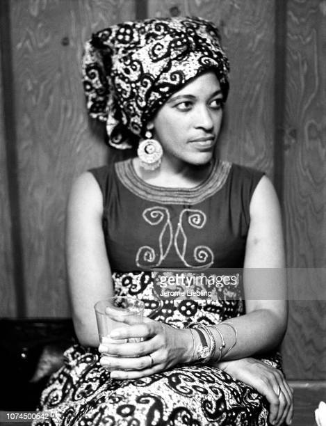 Portrait of American anthropologist and educator Johnnetta Betsch Cole as she sits against a wall holding a glass, Amherst, Massachusetts, 1973. She...