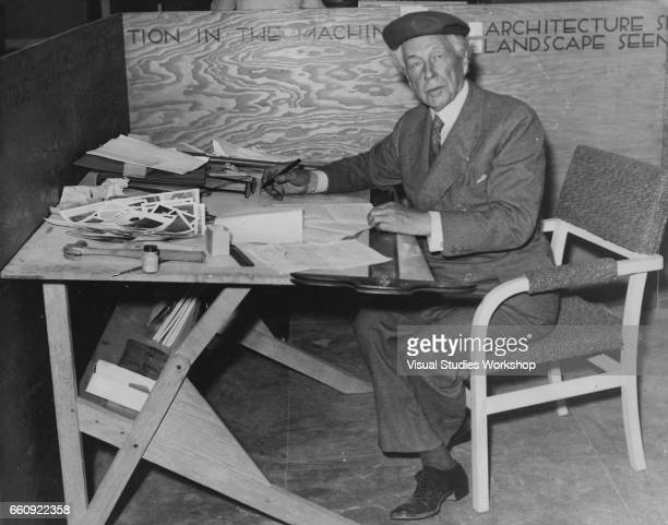 Portrait of American architect Frank Lloyd Wright as he poses at a drafting table during the Industrial Arts Exposition at Rockefeller Center Forum...