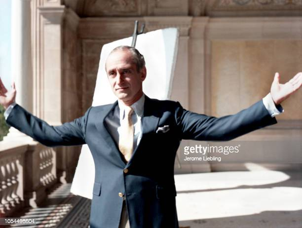 Portrait of American architect Robert AM Stern his arms spread wide as he stands on the loggia of an unidentified building Newport Rhode Island...
