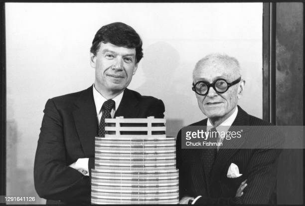 Portrait of American architects and business partners John Burgee and Philip Johnson as they pose, with a model of their Lipstick Building design, in...