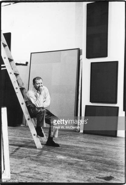 Portrait of American artist Ad Reinhardt rests his chin on his fist as he sits on a ladder New York New York April 1 1961