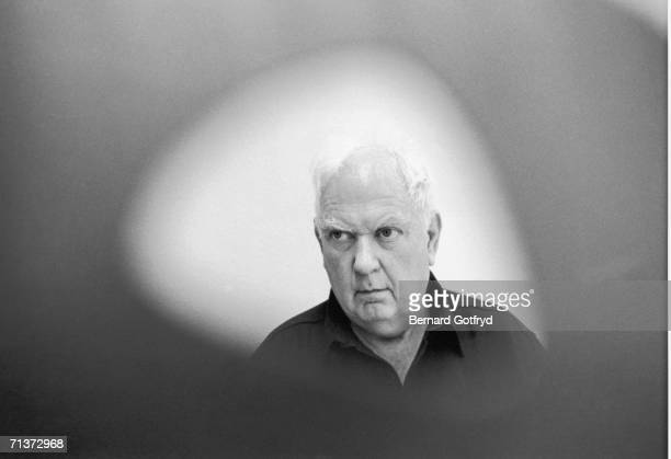 Portrait of American artist and sculptor Alexander Calder seen through an opening in one of his worlks 1970
