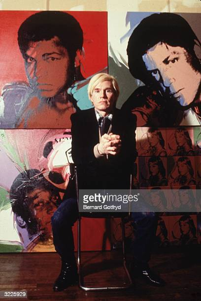 Portrait of American artist Andy Warhol as he sits on a chair in front of his four of his lithograph portraits, late 1970s. The paintings behind him,...