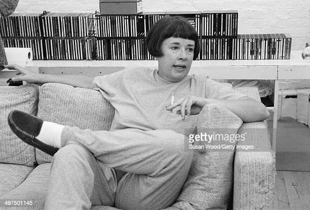 Portrait of American artist Jennifer Bartlett smokes a cigarette as she sits on a couch New York New York 1980s or 1990s
