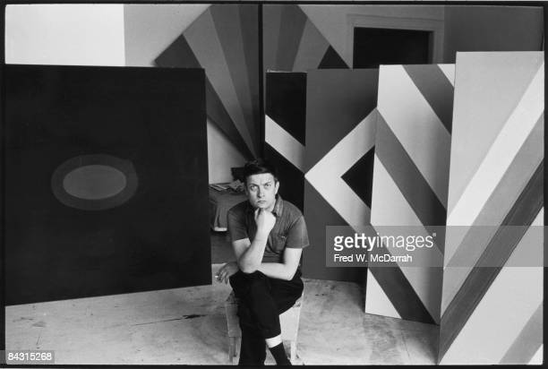 Portrait of American artist Kenneth Noland as he sits on a chair in his studio surrounded by his geometric paintings 1960s
