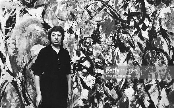 Portrait of American artist Lee Krasner as she poses in front of one of her paintings New York New York 1950s