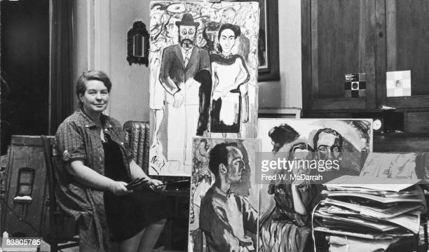 Portrait of American artist painter Alice Neel as she sits in her home a collection of brushes in her hands surrounded by her portraits of other...