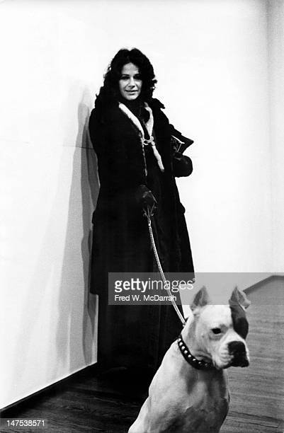 Portrait of American artist Ruth Kligman as she leans against a wall the leash of a dog in her hand New York New York February 13 1974