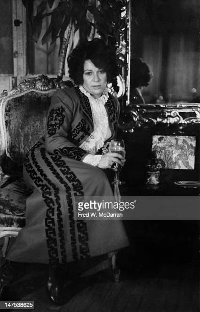 Portrait of American artist Ruth Kligman as she sits on an ornate chair with a wineglass in her hands New York New York December 16 1968