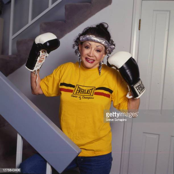 Portrait of American astrologer and tv personality Jacqueline 'Jackie' Stallone wearing boxing gloves as she poses on a staircase in her home Los...
