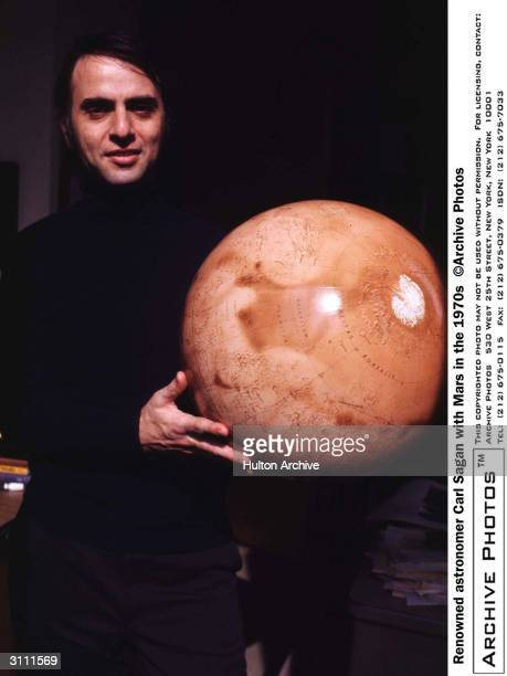 Portrait of American astronomer and author Carl Sagan holding a globe model of the planet Mars 1970s