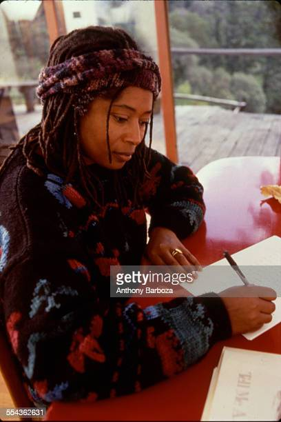Portrait of American author Alice Walker as she writes at her desk 1990s