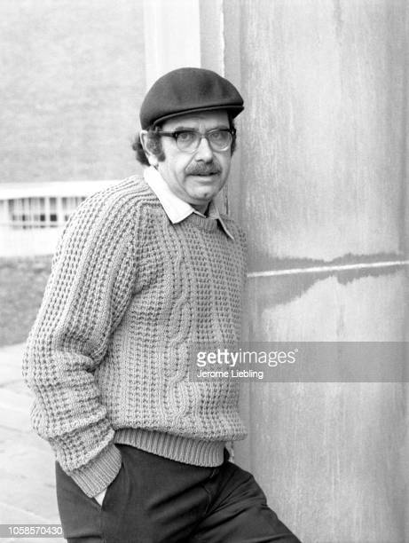Portrait of American author and college professor George Michael Cuomo dressed in a cap and sweater as he leans against an exterior wall Amherst...
