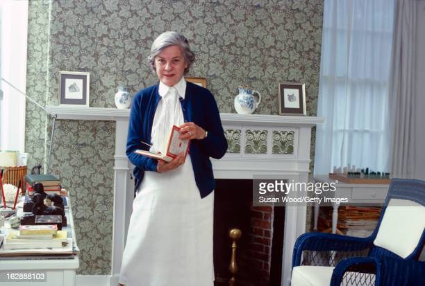 Portrait of American author and critic Mary McCarthy as she holds an open book and stands next to her writing desk in her summer home, Castine,...