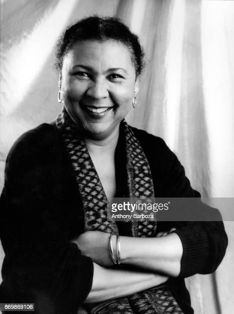 Portrait of American author and feminist bell hooks as she smiles her arms folded New York 1980s