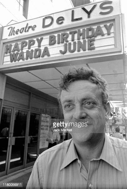 Portrait of American author and playwright Kurt Vonnegut Jr as he poses outside the Theatre de Lys , where the marquee advertises a production of his...