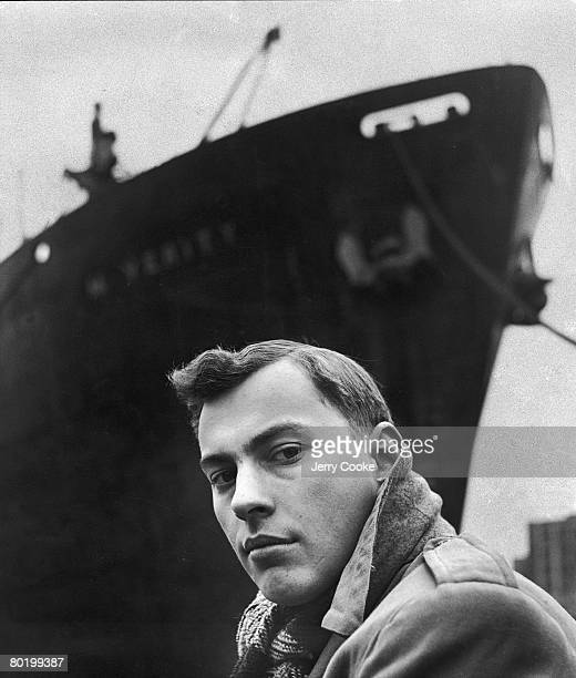 Portrait of American author Gore Vidal as he poses beneath the bow of a large ship, April 1947.
