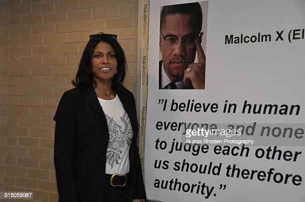 Portrait of American author Ilyasah Shabazz daughter of Malcolm X and Betty Shabazz as she poses beside a quote from father on a poster at Malcolm X...