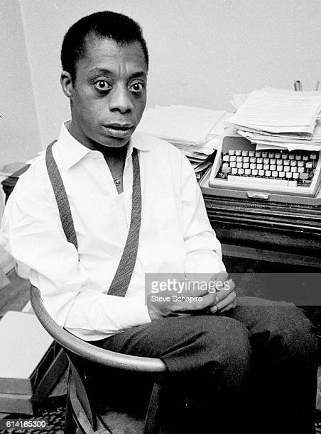 Portrait of American author James Baldwin as he sits beside a desk and typewriter New York 1963