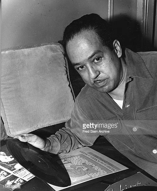 Portrait of American author Langston Hughes , a phonograph record in hand, 1954.