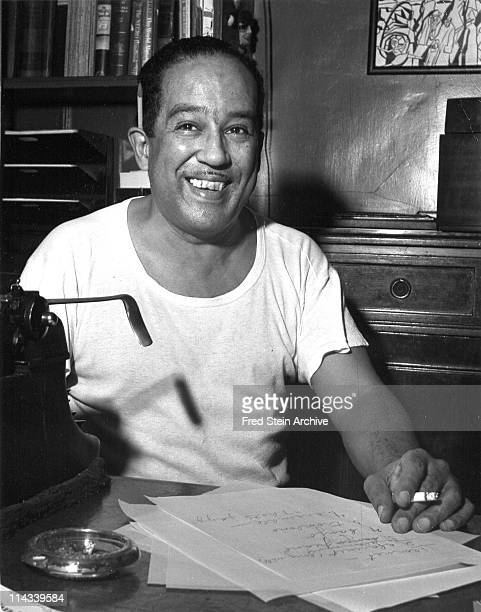 Portrait of American author Langston Hughes as he sits at a desk, 1954.