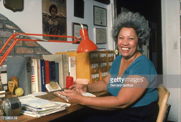 Portrait of American author Toni Morrison smiling and sitting at her desk at home 1980s