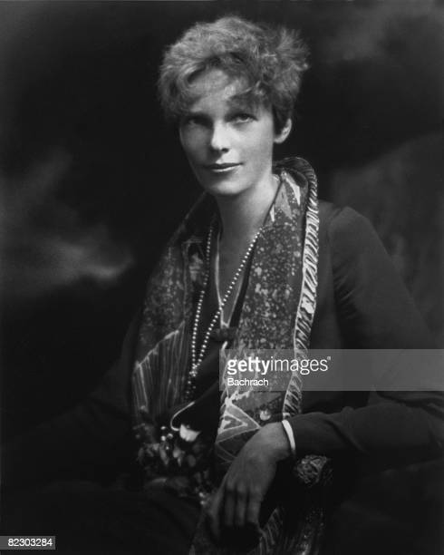 Portrait of American aviator Amelia Earhart as she poses in an armchair a print scarf over her shoulders early 1930s
