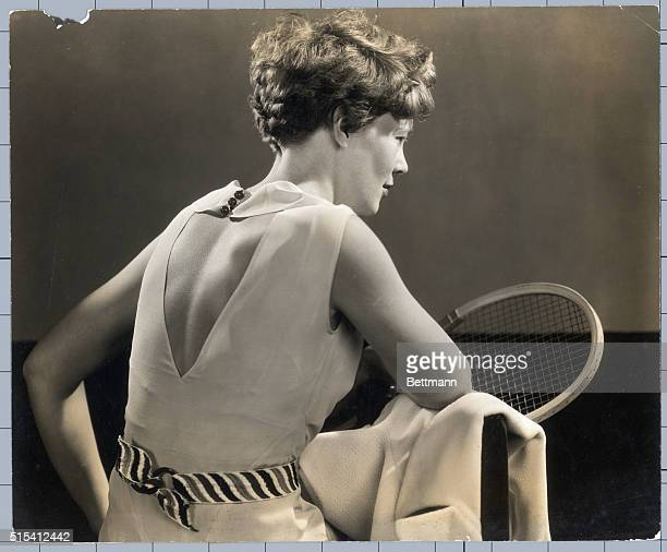 Portrait of American aviatrix Amelia Earhart first woman to cross the Atlantic ocean in airplane She is shown from behind holding a tennis racket...